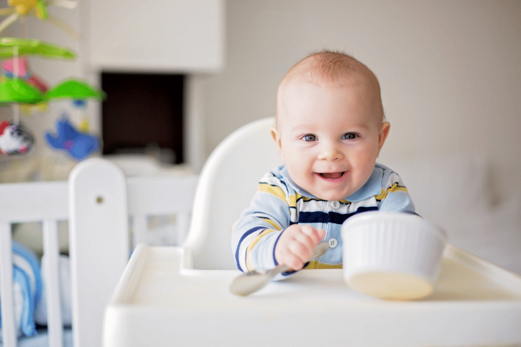 baby holding baby food puree from a jar