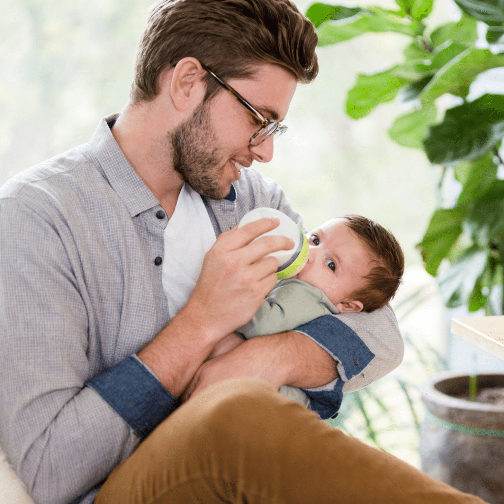 dad feeding baby from a bottle