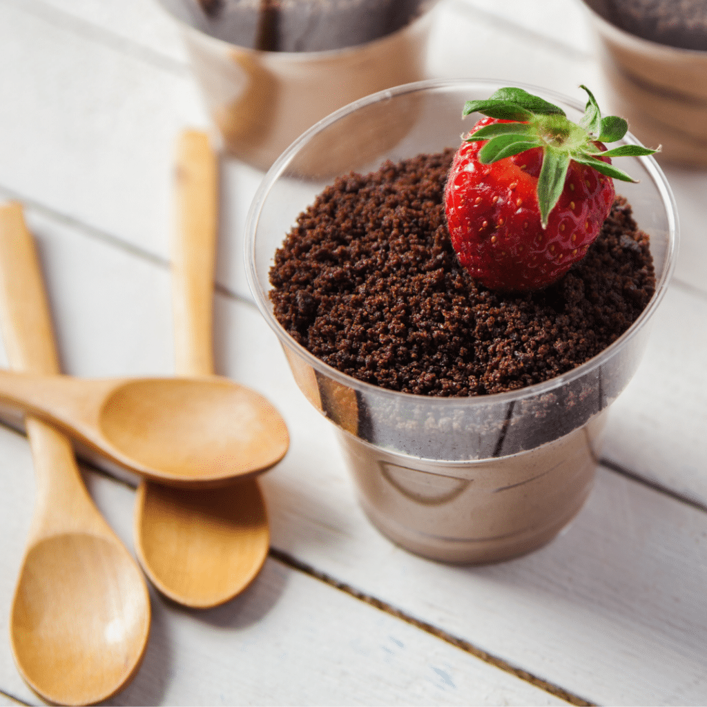 Dirt dessert with a strawberry on top and spoons ready to eat