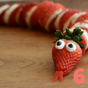 """Step 6 Cut a """"v"""" in one strawberry to create the """"mouth""""; invert the """"v"""" as the tongue"""