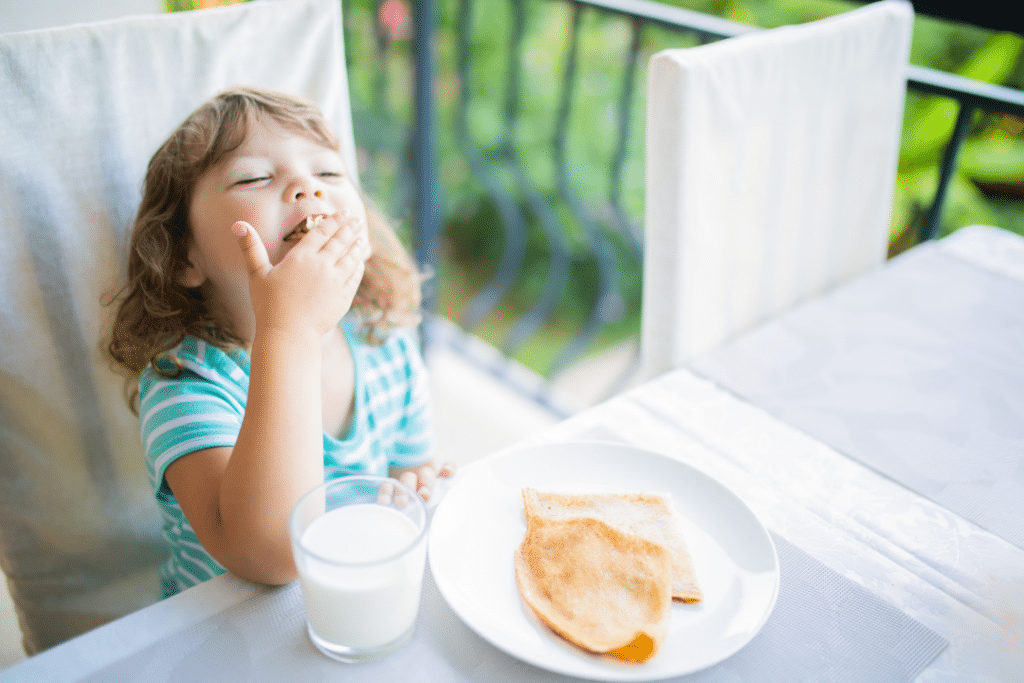 little girl eating snack off a plate
