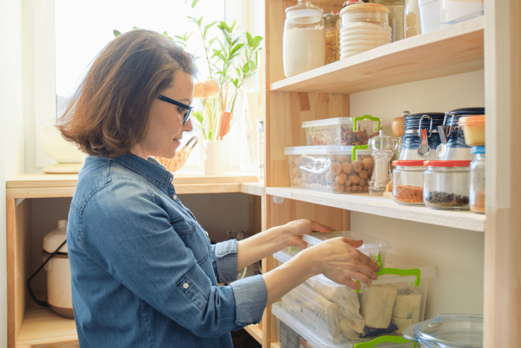 mom in a food allergy friendly pantry closet organizing