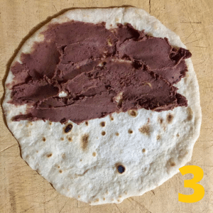 Step 3 Spread the refried beans on the tortilla