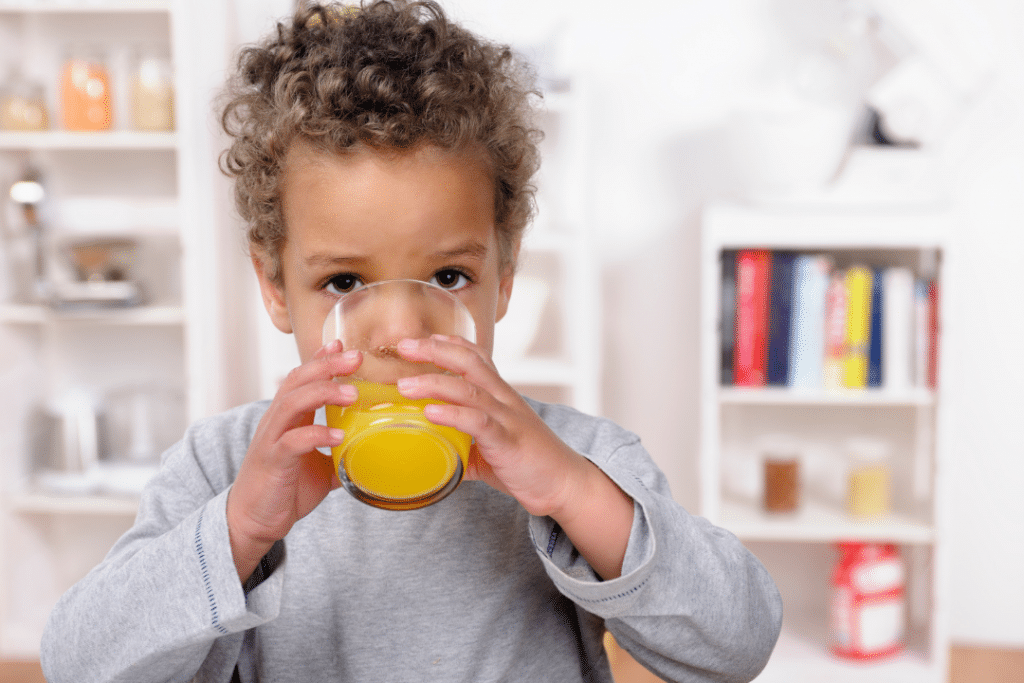 toddler drinking orange juice