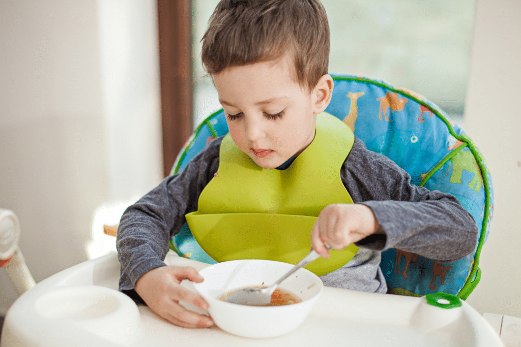 toddler in high chair eating happily