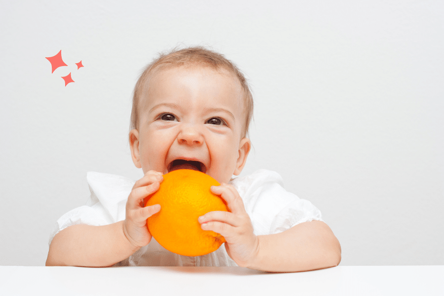 baby with an orange ready to do baby led weaning