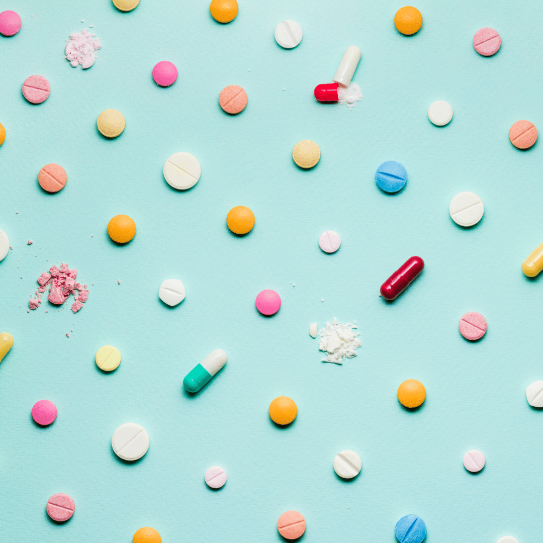 Vitamins displayed in a pattern on a blue background.