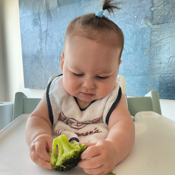 Olivia at 6 months with her first bite of broccoli